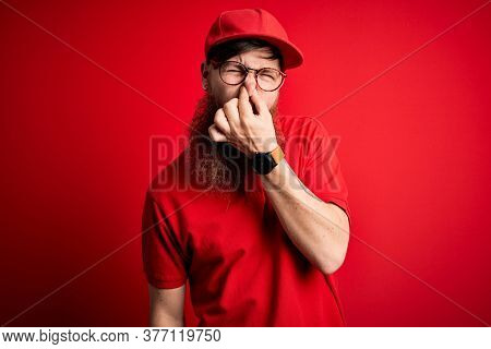Young handsome delivery man wearing glasses and red cap over isolated background smelling something stinky and disgusting, intolerable smell, holding breath with fingers on nose. Bad smell