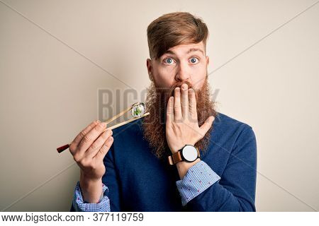 Redhead Irish man with beard eating green maki sushi using chopsticks over yellow background cover mouth with hand shocked with shame for mistake, expression of fear, scared in silence, secret concept