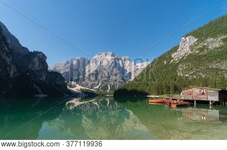 Panoramic View Of Lake Braies And Seekofel Mountain Reflected In The Water With A Hut For Boat Renta
