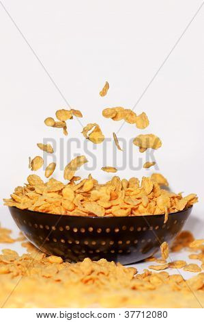 Golden cornflakes falling into bowl