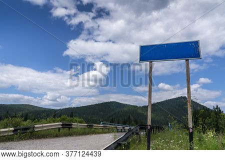 Empty Road Blue Country Sign Pointer On The Background Of Beautiful Nature, Sky And Mountains. Sceni