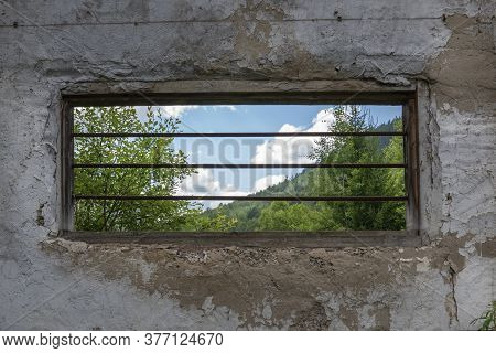 An Elongated Window With Bars In An Old Building Overlooking A Beautiful Forest And Cloudy Sky. Conc