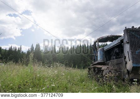 An Old Rusty Crawler Tractor, Abandoned In A Field, Against The Background Of A Pine Forest In Siber