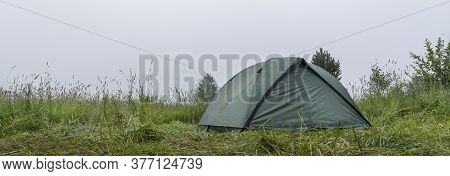 A Green Camping Tent Stands On The Grass. Morning Heavy Fog, Copy Space. Panoramic Photo
