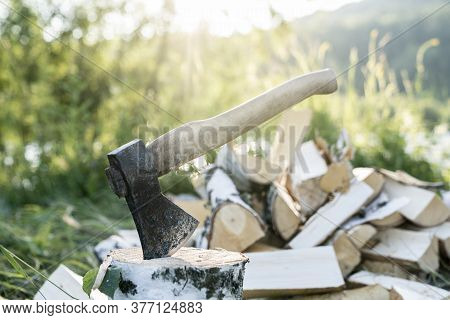 An Axe Stuck In A Log On The Background Of The Forest Close-up