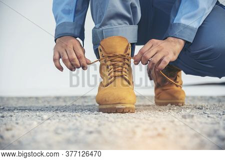 Man Kneel Down And Tie Shoes Industry Boots For Worker. Close Up Shot Of Man Hands Tied Shoestring F