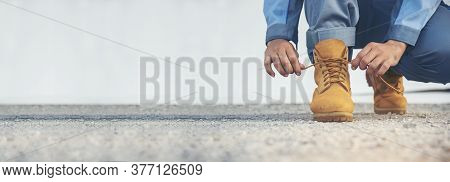 Banner Man Kneel Down Tie Shoes Lace On Industry Worker Boots. Close Up Shot Of Man Hands Tied Shoes