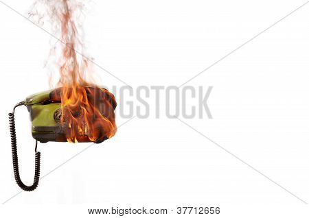 Burning old-fashioned telephone handset and instrument with flames and smoke isolated on white