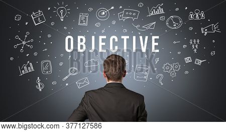 Rear view of a businessman with OBJECTIVE inscription, modern business concept
