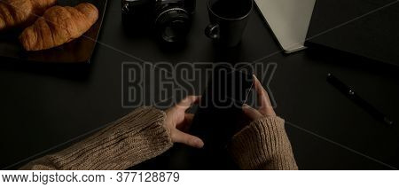 Female Hands Using Smartphone While Sitting At Dark Worktable With With Croissants And Supplies