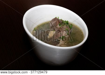 Meat In The Broth With Some Herbs Served In The White Bowl. Side View