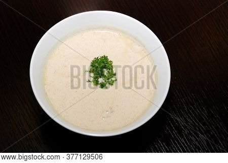 Creamy Soup In The White Bowl With Parsley On The Top. Top View