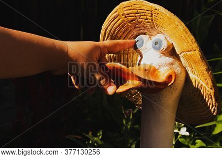 A Child's Hand, A Child's Index Finger Shows The Eye Of A Statuette Of A Goose In A Straw Hat In A S