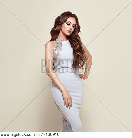 Beautiful Woman In Elegant White Evening Dress. Brunette Girl With Long Healthy And Shiny Curly Hair