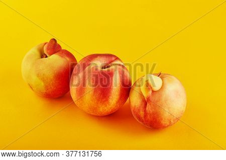 An Ugly Fruit Or Vegetable. Fresh Peach And Two Very Ugly Peach Mutants On An Orange Background. Ugl