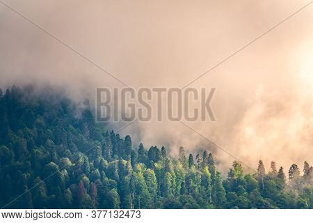 High Mountain With Green Slopes Hidden In Thick Clouds And Fog. Heavy Fog In The Mountains On A Clou