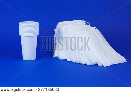 A Stack Of Disposable Medical Masks And A Stack Of Disposable White Plastic Cups On A Blue Backgroun