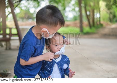 Brother Putting Mask On His Toddler Girl Sister, Siblings Wearing Protective Medical Mask In Public