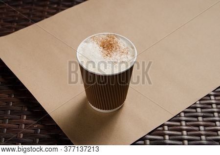 Cappuccino Coffee With Vanilla Crumbs In A Brown Disposable Paper Cup