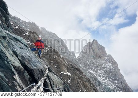 Young Man In Sunglasses And Safety Helmet Holding Fixed Rope While Climbing Mountain. Alpinist Ascen
