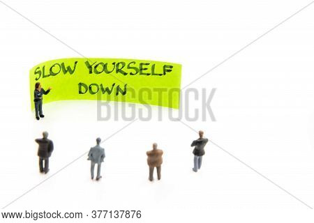 Meeting With Miniature Figurines Posed As Business People Standing Around Post-it Note With Slow You