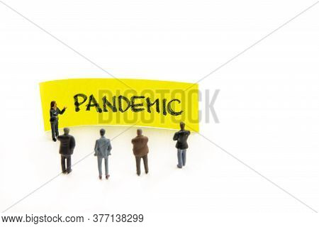 Meeting With Miniature Figurines Posed As Business People Standing Around Post-it Note With Pandemic