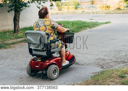Poltava, Ukraine - July 2020 Elderly Woman On E-mobile Vehicle For Disabled Person