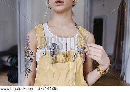 Closeup Young Female Artist Holding Painting Instruments In A Pocket On The Bust Indoors. Tattoos On
