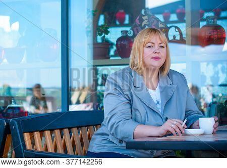 A Pretty Big European Girl With Overweight Smokes In An Outdoor Cafe. Problems Of Smoking Among Wome