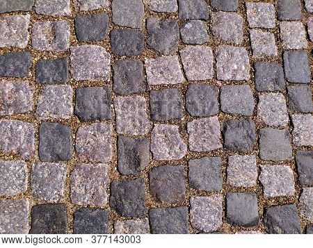 Stone Road Is Grey. The Background Of The Granite Cobblestone Pavement. Abstract Background Of The O