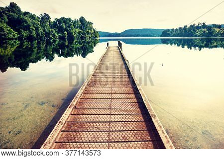 Wooden pier in serenity mountains lake