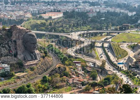 Izmir, Turkey - November 5, 2019: Ataturk Mask, the concrete relief of the head of Mustafa Kemal Ataturk, at the Smyrna Ephesos road in Izmir. Turkish landscape with running train and big interchange
