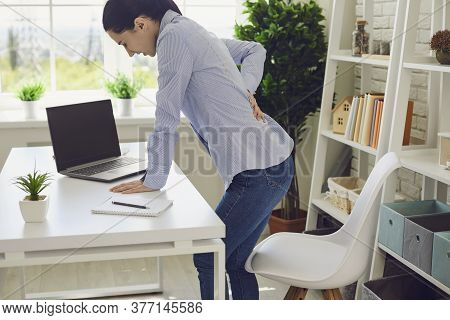 Backache. Woman Suffering From Back Pain At Workplace.
