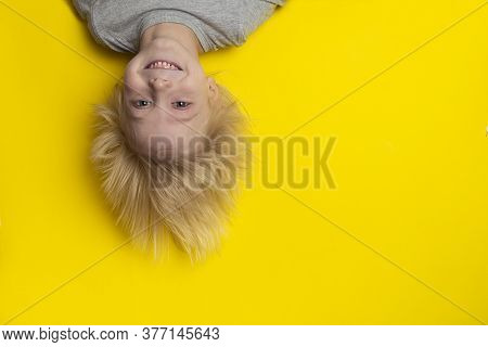 Happy Fair-haired Boy Hanging Upside Down On Yellow Background. Funny Portrait Of Child.