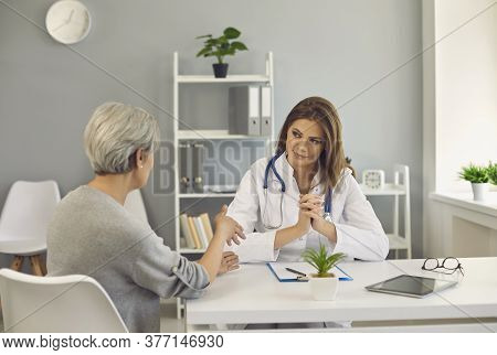 Mature Woman Talking To Medical Doctor At Clinic. Senior Patient Receiving Consultation From Physici