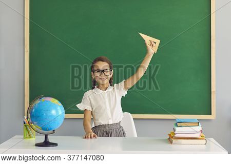 A Schoolgirl With Glasses Is Smiling On The Background Of The School Blackboard. Learning Education