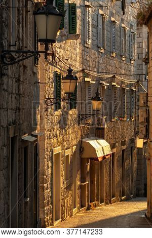 Narrow medieval paved street in old town of Split at sunrise, Croatia