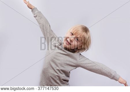 Exciting Fair-haired Boy Playing Airplane. Portrait Of Child On White Background