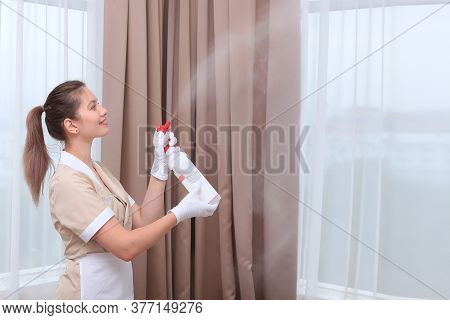 A Uniformed Maid Sprays Air Freshener From A Plastic Bottle. Hands In White Cotton Gloves. Copy Of T