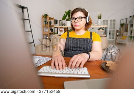 Young serious female with headphones keeping her fingers on keypad and looking at data on computer screen while working at home