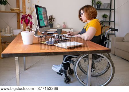 Young disable woman in wheelchair making notes in front of computer monitor while sitting by desk at home during remote lesson