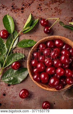 Freshly Picked Cherries With Stem And Leaves On Rusty Metal Surface