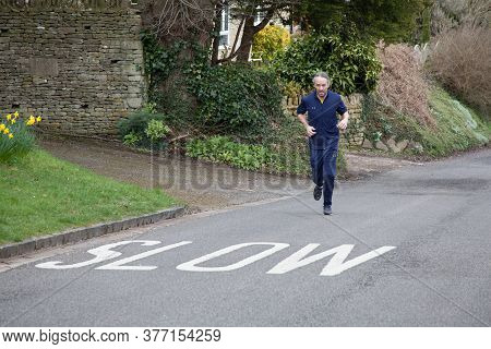 A Fit Man Running In The Road In Burford, Oxfordshire, Uk, Taken 3rd Of March 2020 In Witney, Oxford