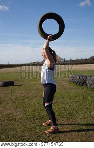 A Woman Exercising On A Farm In The Uk Lifting Heavy Tyres, Taken 16th March 2020 In Abingdon, Oxfor