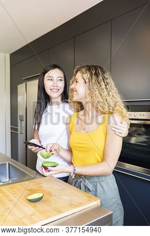 Couple Of Beautiful Woman Looking At Each Other While Holding An Emptied Avocado And A Phone At A Ki