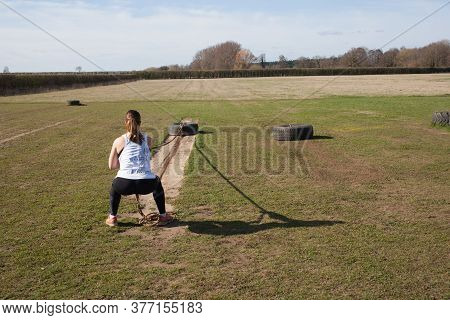 A Woman Exercising On A Farm In The Uk By Pulling A Heavy Tyre By A Long Chain, Taken 16th March 202