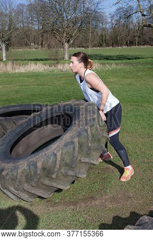 A Woman Lifting Heavy Tyres On A Farm, Taken 16th March 2020 In Abingdon, Oxfordshire In The Uk