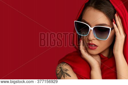 Portrait Of Gorgeous Sexy Woman With Luxurious Make-up In White Sunglasses And Red Headscarf On Red