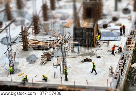 The Workers Are Working At The Construction Site. Tilt Shift Miniature Toy Effect