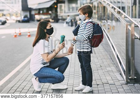 The Mother Gives The Child A Bottle Of Water And Accompanies Him To School. A Boy And His Mother In